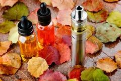 在木桌上的电子香烟和vape液体与秋叶 免版税库存图片