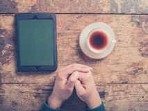 在木桌上的男性手用咖啡和片剂 库存图片