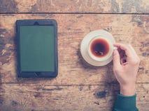 在木桌上的男性手用咖啡和片剂 免版税库存图片