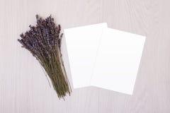 在木桌上的白纸用淡紫色 砖灰色纸棍子磁带墙壁白色 明信片 库存照片