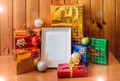 在木桌上的白色框架和圣诞节礼物 免版税库存图片