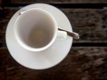 在木桌上的白色空的咖啡杯 库存图片
