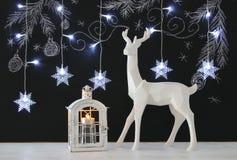 在木桌上的白色驯鹿在与手拉的白垩例证的黑板背景 免版税库存图片
