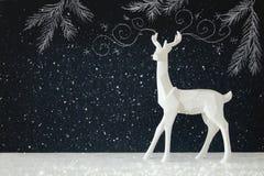 在木桌上的白色驯鹿在与手拉的白垩例证的黑板背景 库存图片