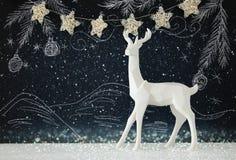 在木桌上的白色驯鹿在黑板背景whith手拉的白垩例证 免版税图库摄影