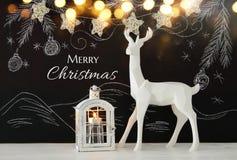 在木桌上的白色驯鹿在黑板背景whith手拉的白垩例证 免版税库存照片