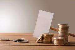 在木桌上的硬币与横幅和棕色背景 免版税库存照片