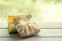 在木桌上的礼物盒在雨天窗口背景 库存图片