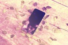 在木桌上的空白的手机屏幕与叶子 免版税库存图片