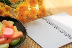 在木桌上的空白的笔记本和果冻糖果 库存照片