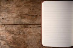 在木桌上的空白的笔记本 图库摄影