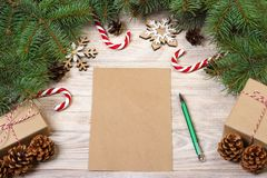在木桌上的空的圣诞卡用圣诞节糖果和礼物盒 库存照片