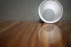 在木桌上的空的塑料杯子身分 免版税库存照片