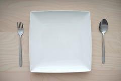 在木桌上的空的方形的板材与叉子和匙子 免版税库存照片