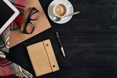 在木桌上的笔记本与此外咖啡杯、片剂和玻璃在早晨时间 免版税库存图片