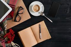 在木桌上的笔记本与此外咖啡杯、片剂和玻璃在早晨时间 库存照片
