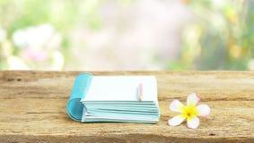 在木桌上的笔记本和赤素馨花花 库存照片