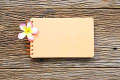 在木桌上的笔记本和赤素馨花花 免版税库存图片