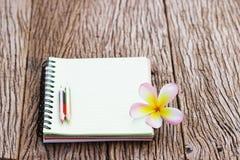 在木桌上的笔记本和赤素馨花花 免版税库存照片