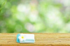 在木桌上的笔记本和赤素馨花花 免版税图库摄影