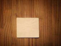 在木桌上的米黄鸡尾酒餐巾 库存照片
