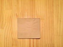 在木桌上的米黄鸡尾酒餐巾 免版税库存图片