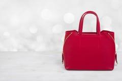 在木桌上的红色女性皮革提包在抽象背景 库存图片