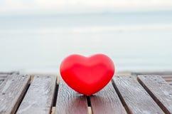 在木桌上的红色心脏在海滩 库存照片