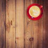 在木桌上的红色杯子和拿铁咖啡 库存图片