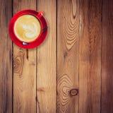 在木桌上的红色杯子和拿铁咖啡 图库摄影