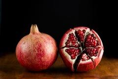 在木桌上的红色水多的石榴果子 免版税库存图片