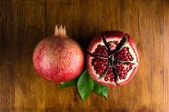 在木桌上的红色水多的石榴果子 免版税库存照片