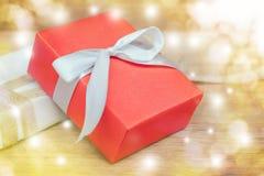 在木桌上的红色礼物盒白色丝带有与拷贝空间的金黄bokeh装饰背景 免版税库存图片