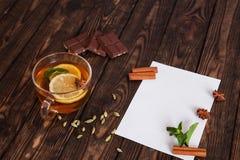 在木桌上的纸与一个杯子茶 免版税库存照片