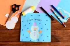 在木桌上的纸雪人应用程序卡 创造冬天工艺的工具和材料 简单的工艺 图库摄影