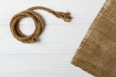 在木桌上的绳索和粗麻布织品 免版税库存照片