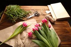 在木桌上的美丽的桃红色郁金香、纸和亚麻布串 图库摄影