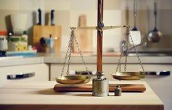 在木桌上的老平衡在厨房背景 免版税图库摄影