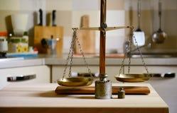 在木桌上的老平衡在厨房背景 免版税库存照片