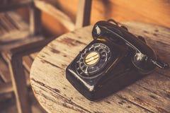 在木桌上的老电话黑色颜色 经典减速火箭的葡萄酒样式 免版税库存照片