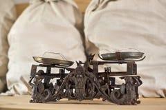 在木桌上的老经典葡萄酒贸易标度与在背景的袋子 图库摄影