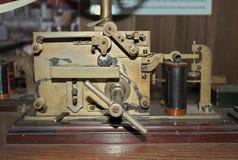 在木桌上的老莫尔斯电报键通信机 库存照片