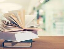 在木桌上的老被堆积的书 免版税库存照片
