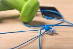 在木桌上的耳机与被弄脏的哑铃和智能手机 库存照片