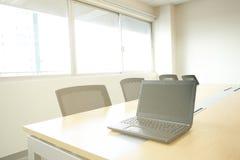 在木桌上的膝上型计算机在从窗口的会议室阳光下 免版税库存照片