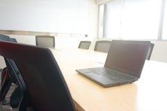在木桌上的膝上型计算机在从窗口的会议室阳光下 库存图片