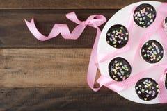 在木桌上的自创杯形蛋糕与桃红色丝带 免版税库存照片
