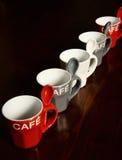 在木桌上的色的咖啡杯 库存图片