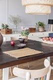 在木桌上的花在现代明亮的餐厅内部的灯下与椅子 实际照片 库存图片