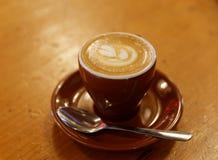 在木桌上的花梢咖啡拿铁Macchiato 免版税库存照片